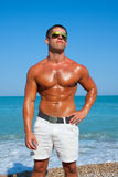 Muscular brutal man on the beach Royalty Free Stock Images