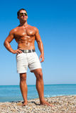 Muscular brutal man on the beach Stock Photos