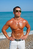 Muscular brutal man on the beach Royalty Free Stock Image