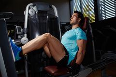 Muscular build man doing legs press exercise in fitness center Stock Photography