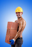 Muscular builder with bricks against gradient Royalty Free Stock Photos