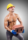 Muscular builder with bricks on white Stock Photo