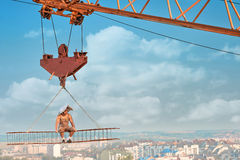 Muscular builder resting and sitting on high construction. Stock Image