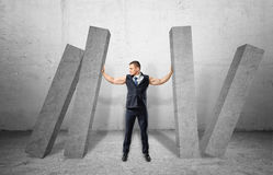 Muscular businessman full-height holding concrete four columns falling on him Stock Image