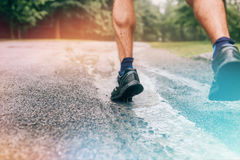 Muscular calves of fit male jogger training for cross country forest trail race in the rain on a nature trail. Stock Photography