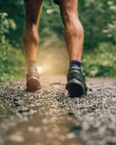 Muscular calves of fit male jogger training for cross country forest trail race in the rain on a nature trail. Royalty Free Stock Image