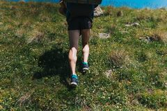 Muscular calves of a young athlete running with backpack up a mo. Untain path, ultramarathon and skyranning Royalty Free Stock Images