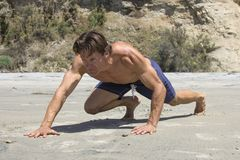 Muscular Caucasian man doing tough bear crawl workout stock image