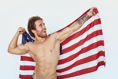 Muscular cheerful man posing with flag. Young handsome man posing shirtless with American flag looking cheerfully away Stock Photos