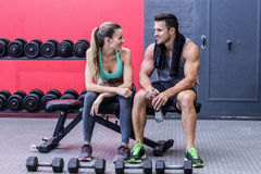 Muscular couple discussing on a bench. At the crossfit gym Stock Photography