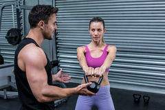 A muscular couple discussing together. Muscular couple discussing together while lifting kettlebells Stock Photo
