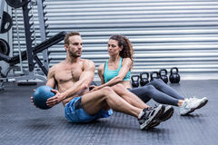 Muscular couple doing abdominal ball exercise Royalty Free Stock Photography