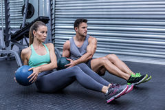 Muscular couple doing abdominal ball exercise stock images