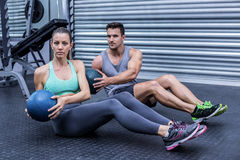 Muscular couple doing abdominal ball exercise. Portrait of muscular couple doing abdominal ball exercise royalty free stock photo