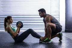 Muscular couple doing abdominal ball exercise stock image