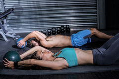 Muscular couple doing abdominal crunch Stock Photography