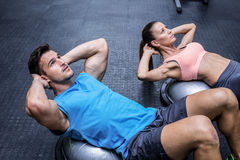Muscular couple doing abdominal crunch Royalty Free Stock Images