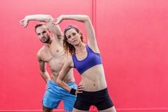 Muscular couple doing arms stretching Royalty Free Stock Photos