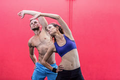 Muscular couple doing arms stretching Stock Images