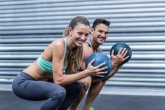 Muscular couple doing ball exercise Stock Photo