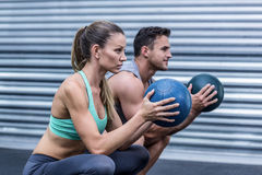 Muscular couple doing ball exercise Royalty Free Stock Images