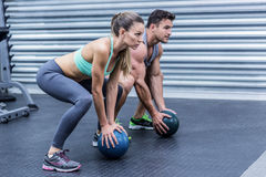 Muscular couple doing ball exercise stock photos