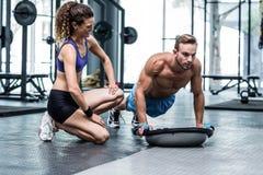 Muscular couple doing bosu ball exercises Royalty Free Stock Photos