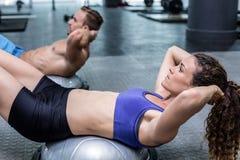 Muscular couple doing bosu ball exercises Stock Photography