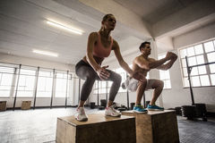 Muscular couple doing jumping squats Royalty Free Stock Photos