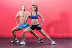 Muscular couple doing leg stretching Stock Image