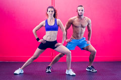 Muscular couple doing leg stretching Royalty Free Stock Images