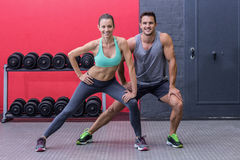 Muscular couple doing leg stretchings Royalty Free Stock Image