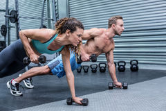 Muscular couple doing plank exercise together Royalty Free Stock Images