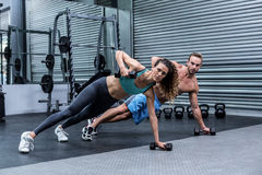 Muscular couple doing plank exercise together Royalty Free Stock Photo