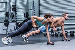 Muscular couple doing plank exercise together Stock Photo