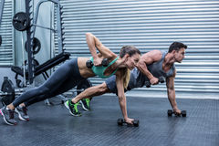 Muscular couple doing plank exercise together. Muscular couple doing plank exercise while lifting weights royalty free stock photo