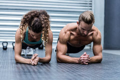 Muscular couple doing planking exercises Stock Image