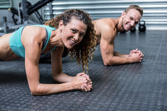 Muscular couple doing planking exercises Stock Photo