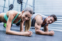 Muscular couple doing planking exercises royalty free stock image