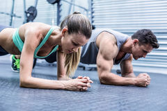Muscular couple doing planking exercises Royalty Free Stock Photography