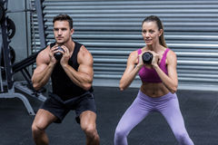 Muscular couple exercising with kettlebells Royalty Free Stock Images
