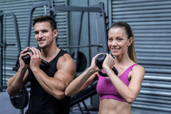 Muscular couple exercising with kettlebells Royalty Free Stock Photos
