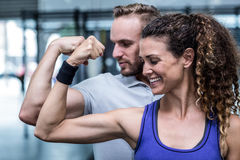 A muscular couple flexing biceps Stock Images