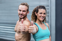 Muscular couple gesturing thumbs up Stock Images