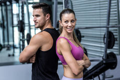 Muscular couple giving back to back. With arm crossed Royalty Free Stock Photo