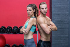 Muscular couple giving back to back. Serious muscular couple giving back to back Royalty Free Stock Photo