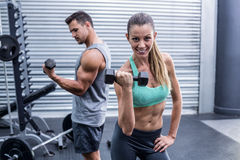 A muscular couple lifting dumbbells royalty free stock photography