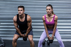 A muscular couple lifting kettlebells Royalty Free Stock Photos