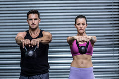 A muscular couple lifting kettlebells Royalty Free Stock Image