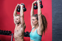 A muscular couple lifting kettlebells Stock Images